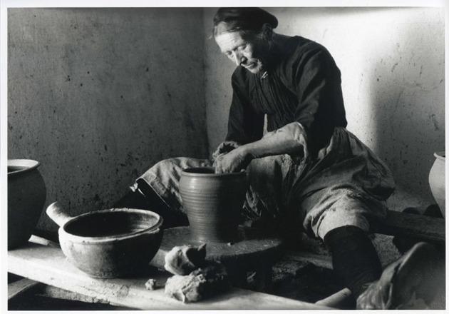 Potière de Saint-Jean-la-Poterie travaillant au tour à bâton.